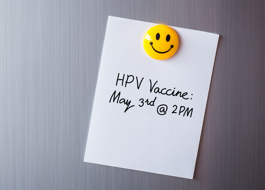 Image Of A Post-It Note On A Fridge With A Smiley Face Magnet With A Date And Time Written On It For An HPV Vaccination Appointment