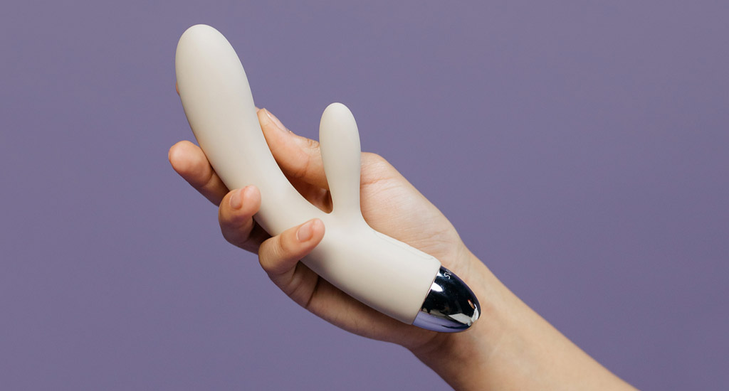 Close Up Photograph Of Hand Holding Ivory Rabbit Vibrator Against Purple Background