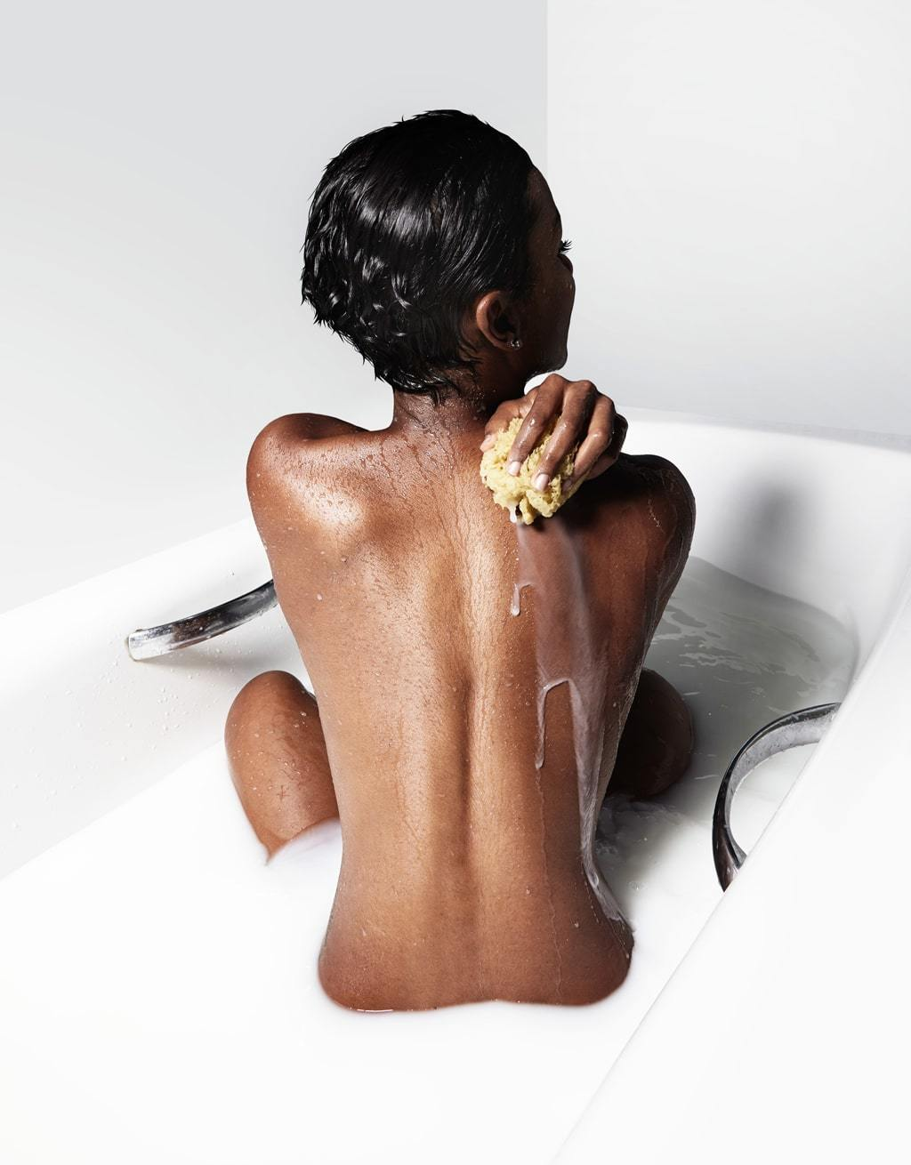 African American Woman In A Bath of Milk Wih Her Back Exposed Signifying The Appeal of A Man Finishing Inside