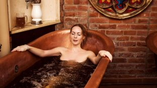 Photo Of A Woman Relaxing In A Copper Bathtub Spa Filled With Beer