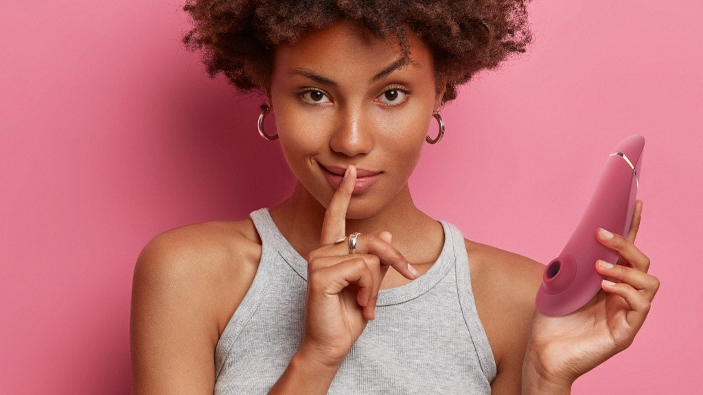 """Photograph Of Woman With """"Hush"""" Finger Over Mouth, Holding Vibrator In Other Hand"""