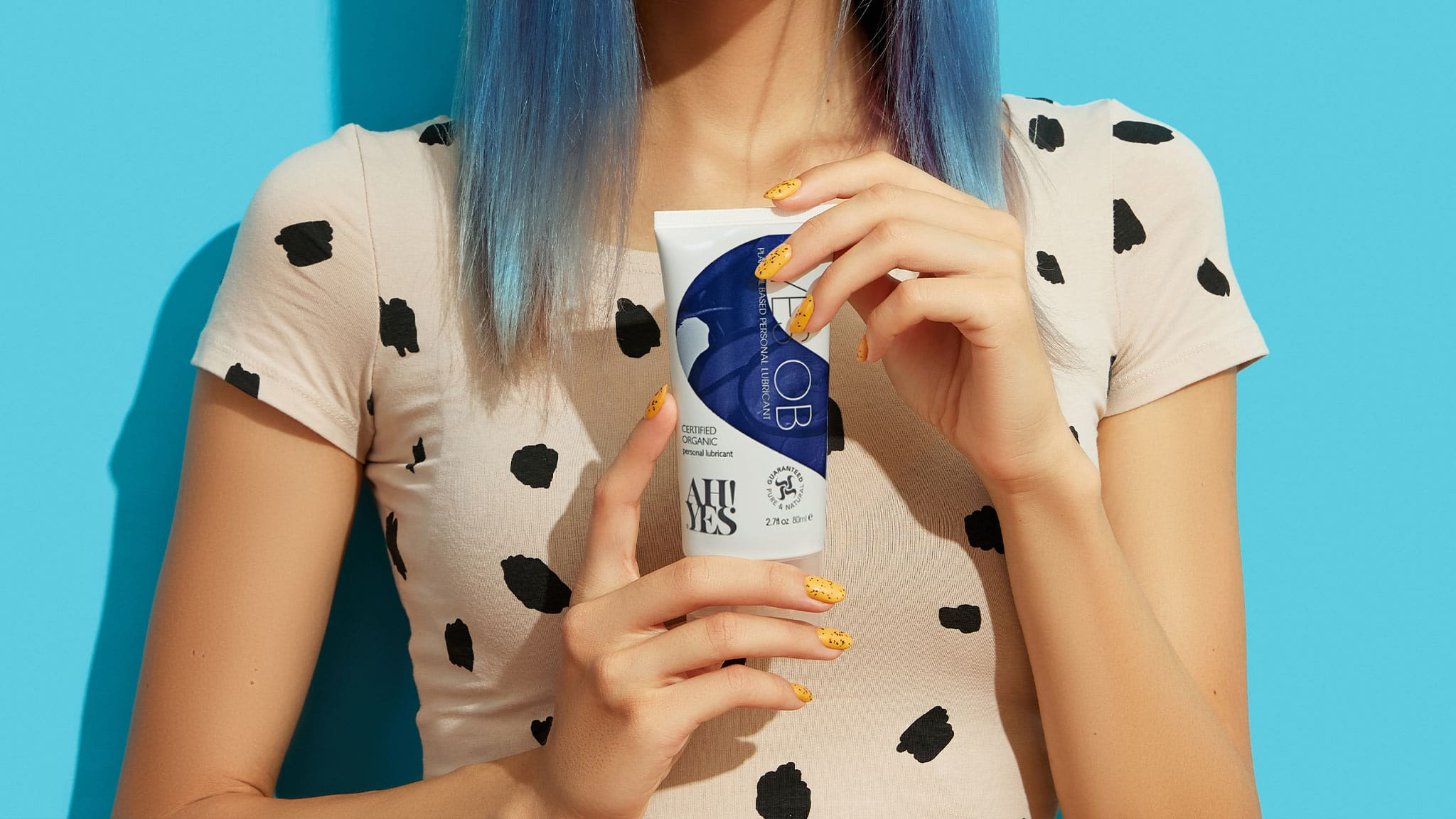 Photograph Of Blue-Haired Woman Holding A Bottle Of AH! YES OB Oil-Based Lubricant