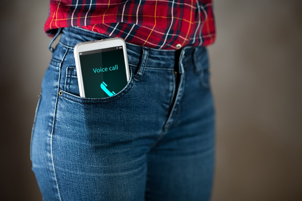 Closeup Photograph Of Ringing And Vibrating Cell Phone In Front Pocket Of A Woman's Blue Jeans
