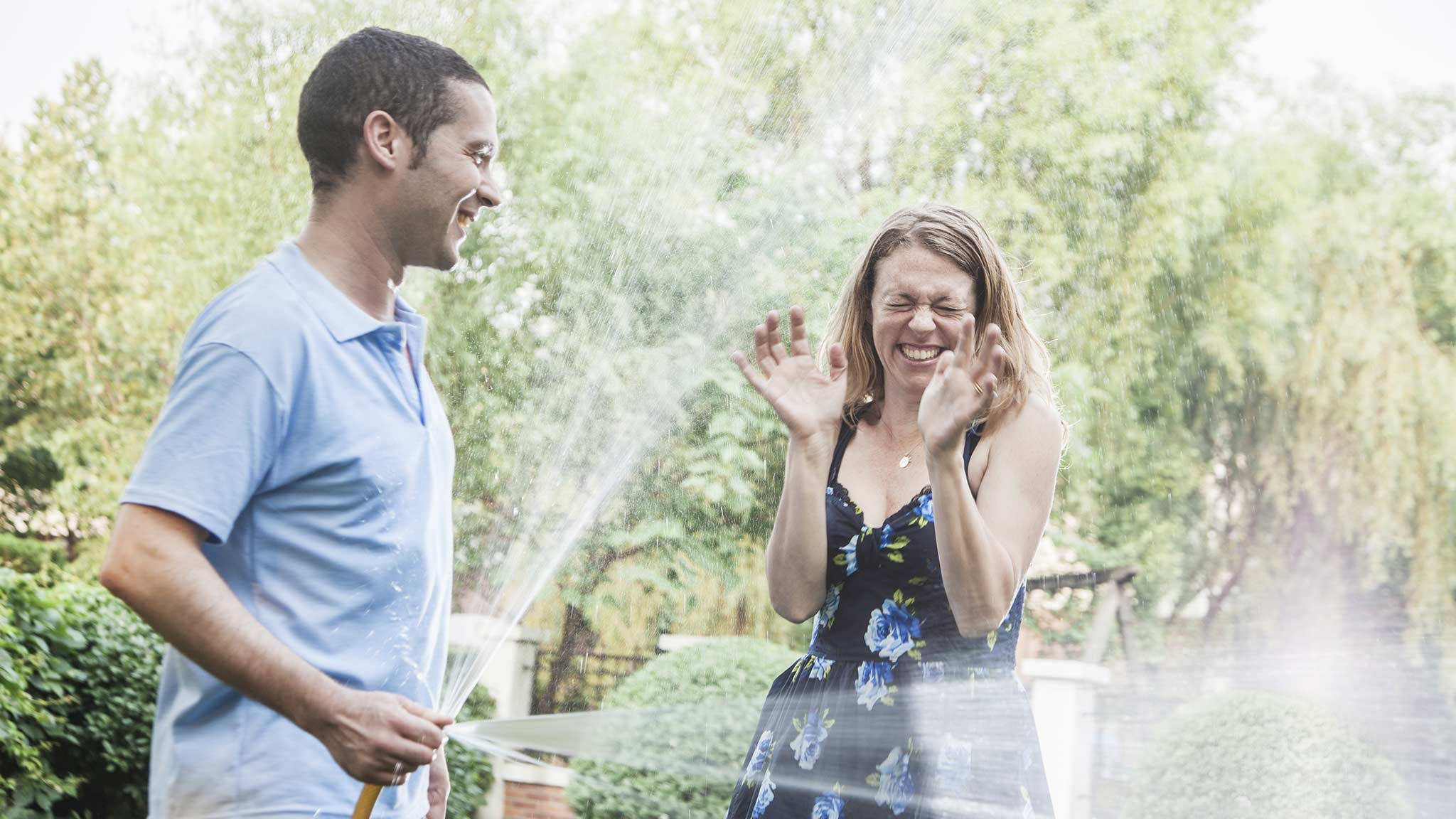 Photograph Of Caucasian Man Playfully Spraying Caucasian Woman With A Water Hose
