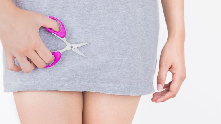 Closeup Photo Of Woman's Hips/Thighs As She Holds Small Open Scissors Near Her Crotch