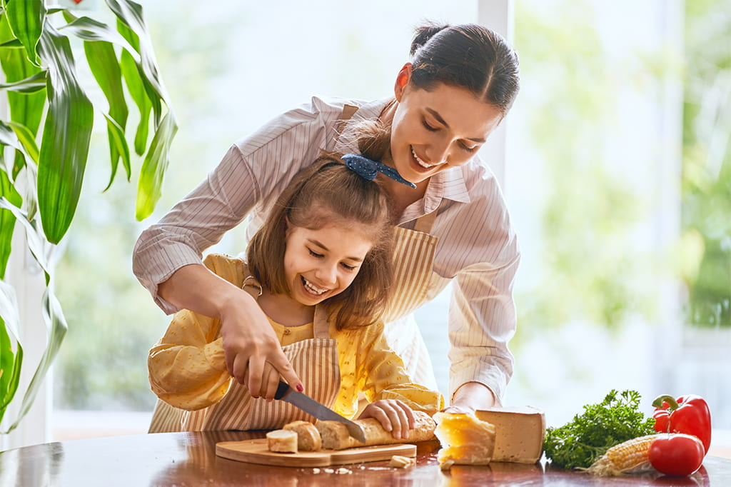 Image Of A Mother And Daughter Smiling While The Mom Helps The Daughter Cut A Piece Of Bread