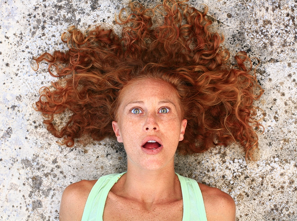 Photo Of A Woman On The Ground From The Neck Up With Red Hair Showing An Expression Of Disbelief And Pleasure
