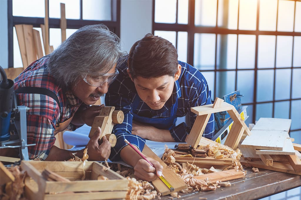 Image Of An Asian Teenager And Hise Father Working Together In A Wood Shop