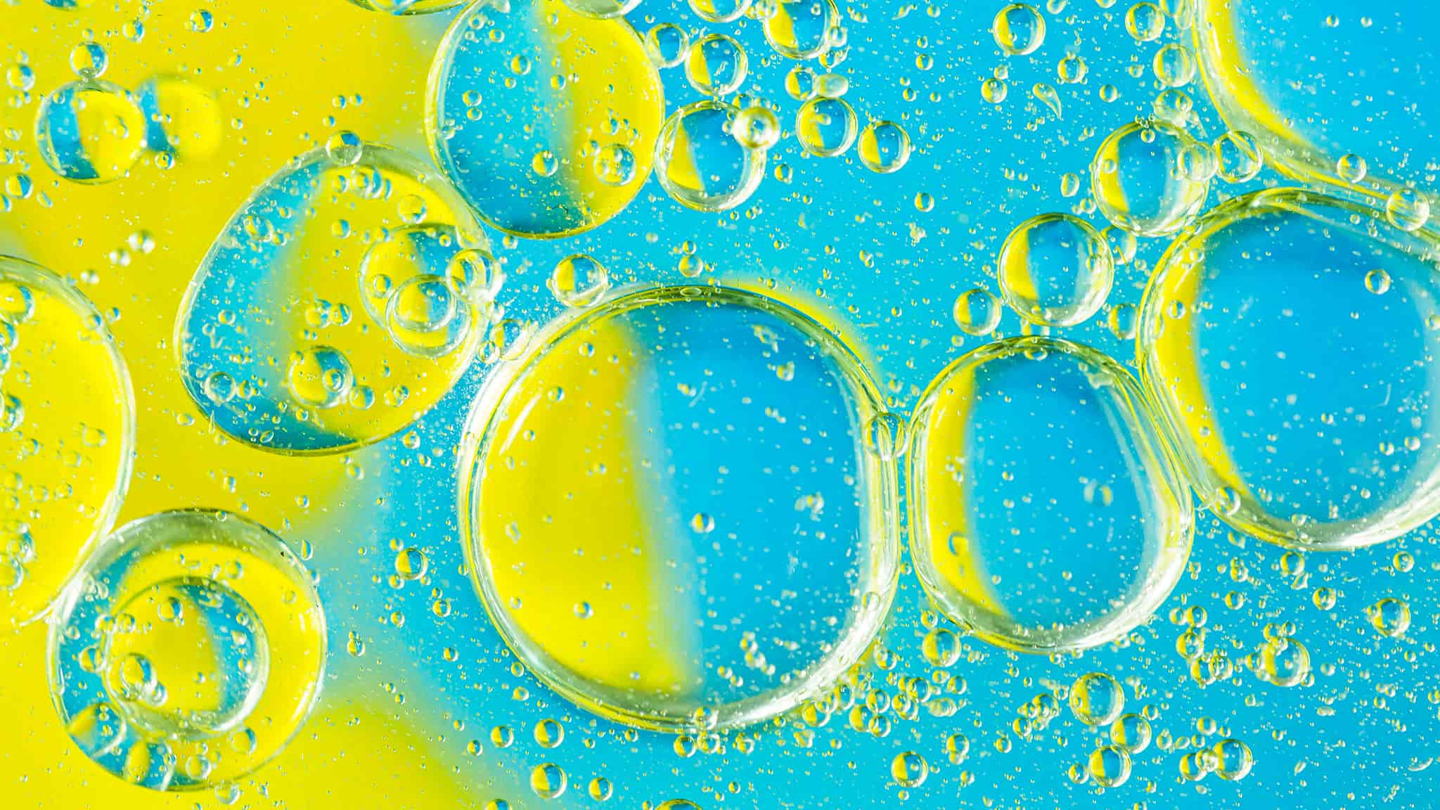 Macro Image Of Yellow And Blue Liquid Bubbles, Silicone Oil Mixing With Water Concept