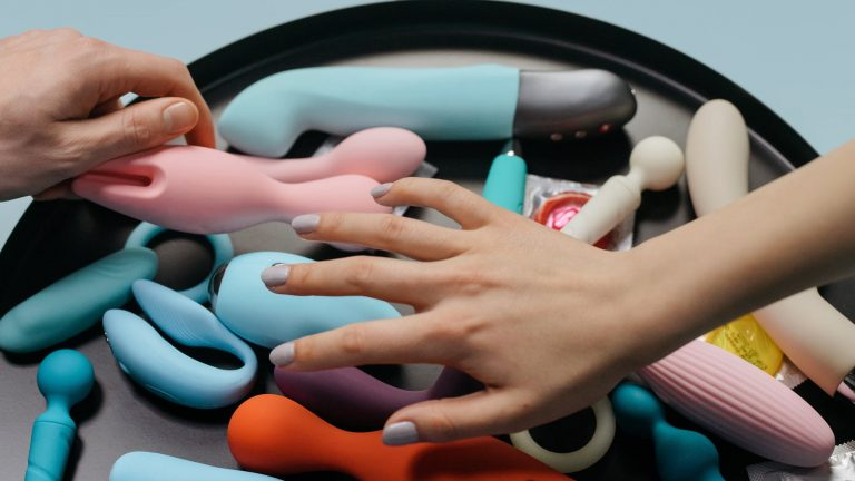 Photograph Of Two Hands Reaching Across A Variety Of Vibrators