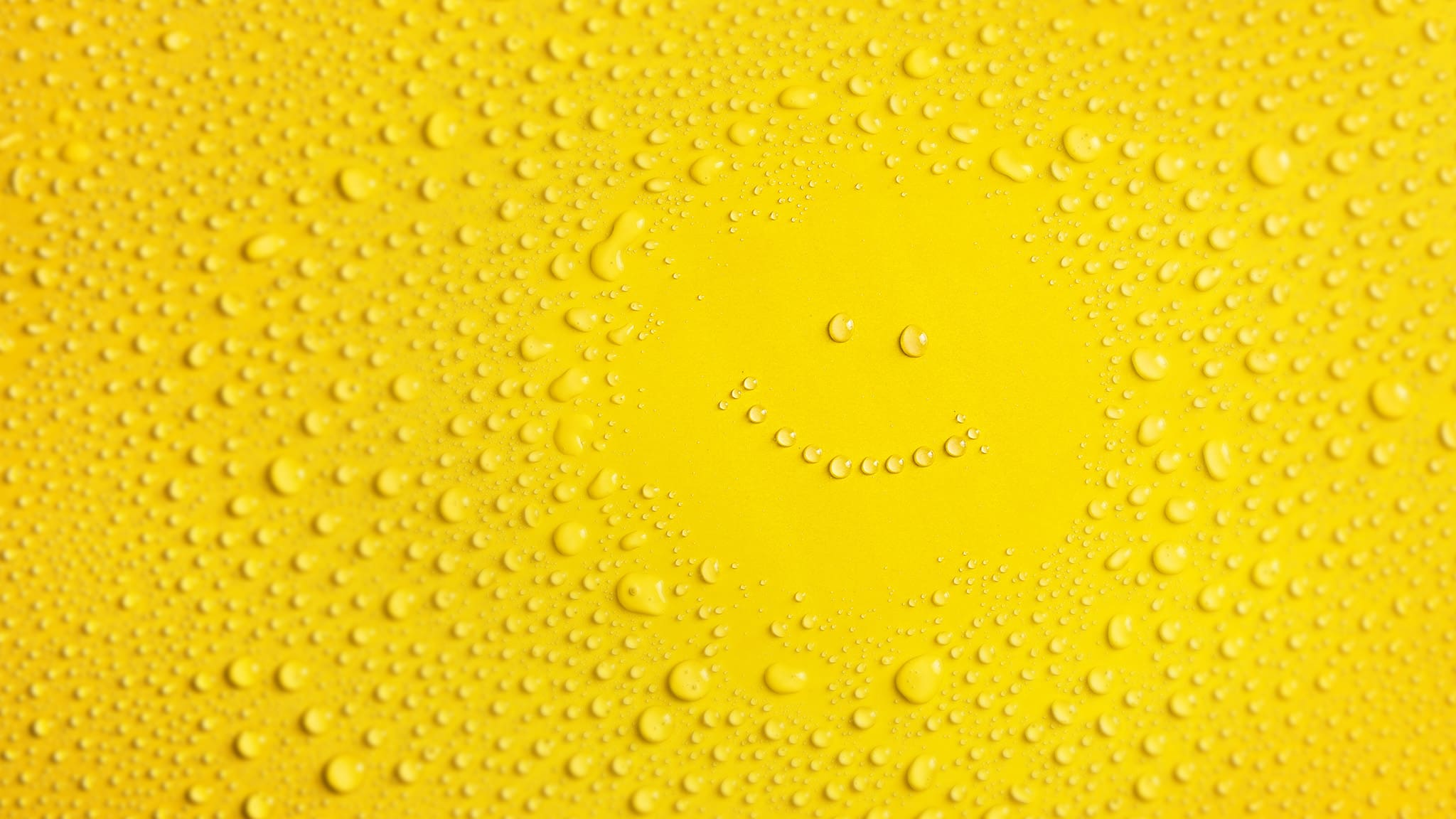 Yellow Background Covered In Water Droplets With A Smiley Face Of Droplets In The Center