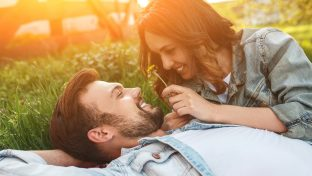 Happy Couple Laying In Grass Smiling Looking At Each Other With Orange Glow Of The Sunset