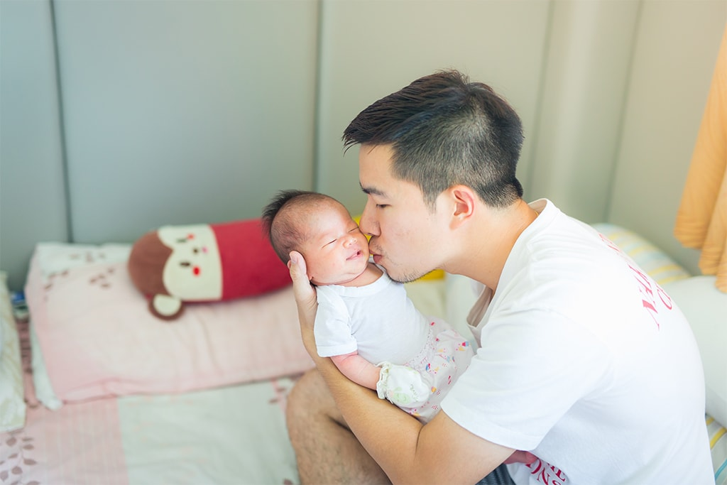 Asian Man Holding A Newborn Baby While Kissing It