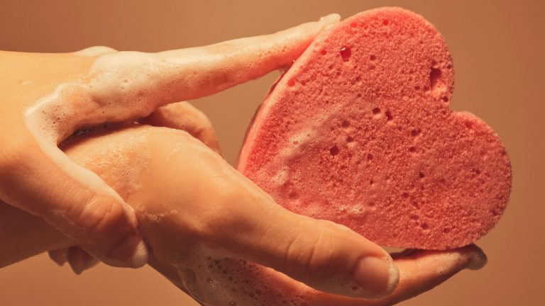 Close Up Photograph Of Woman Holding Soapy, Heart-Shaped Sponge In Her Hands