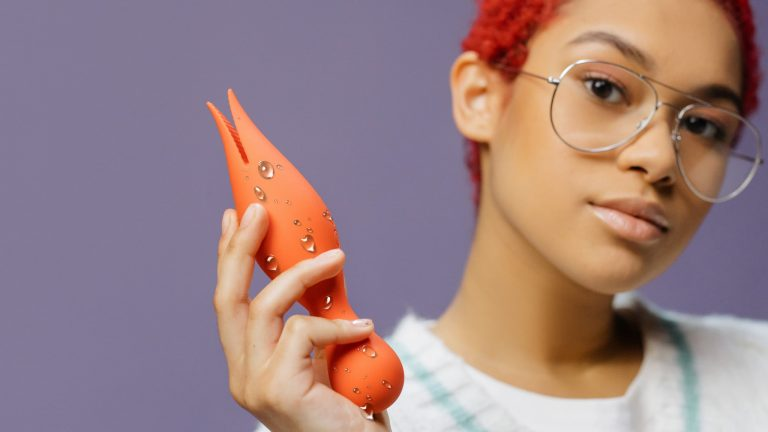 Photograph Of Young Woman Holding Wet, Orange Sex Toy