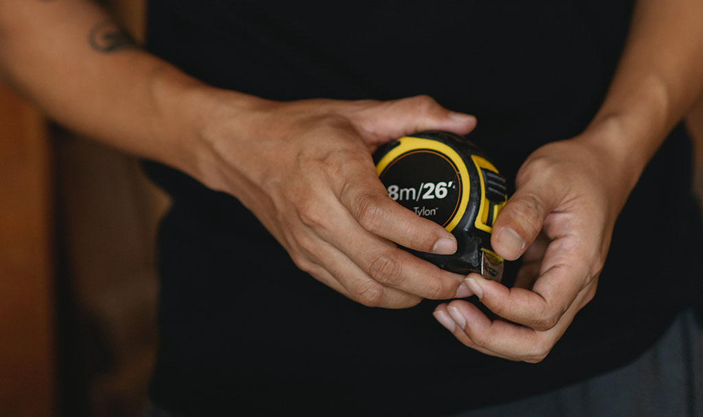 Closeup Photograph Of Man Holding Measuring Tape Near Waist