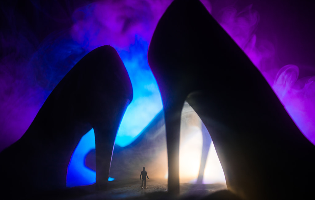Surreal Concept, Silhouette Of Tiny Man Surrounded By Three Giant High Heel Shoes Against Purple And Blue Smoky Light