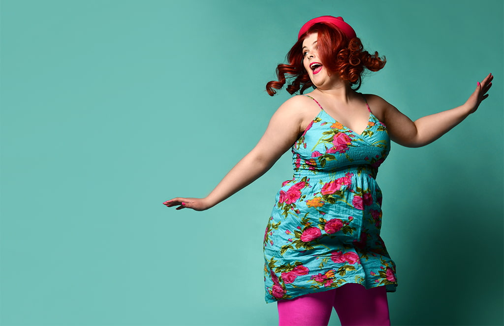 Photograph Of Red-Headed Woman With Large Breasts, Twirling With Arms Akimbo