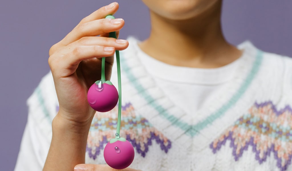 Close Up Photograph Of Woman Holding Wet Ben Wa Balls That Look Like Cherries