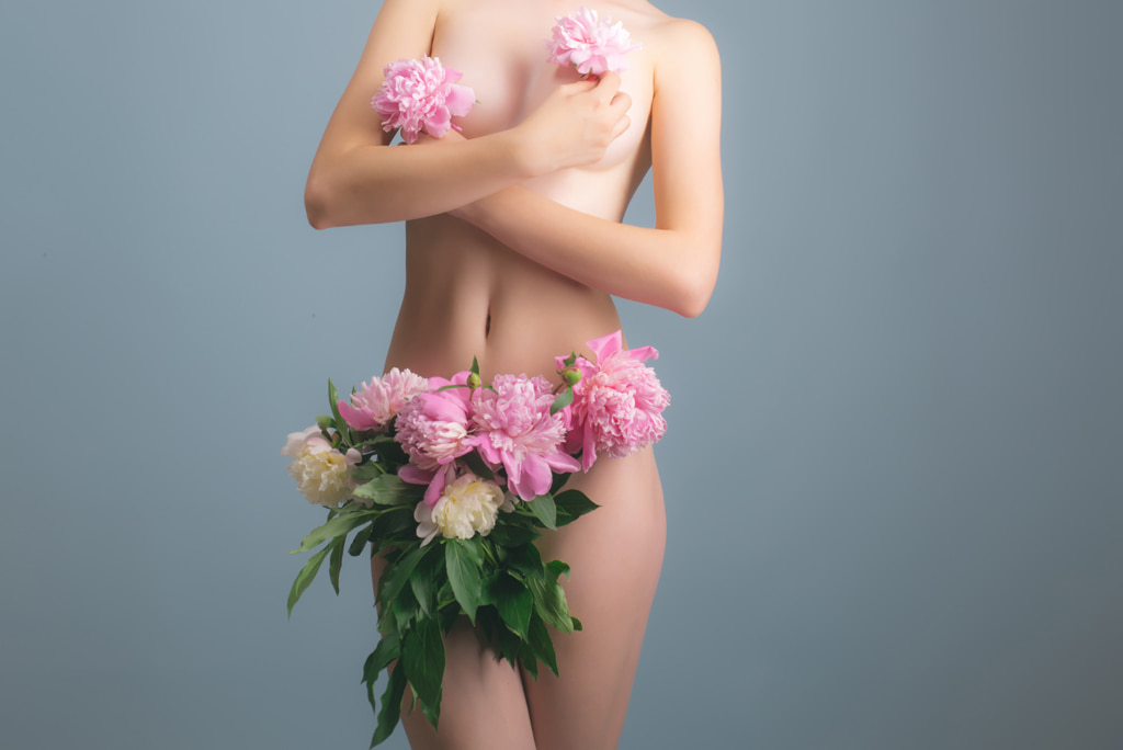 Nude Female Body With Flowers Covering Breasts And Genitals