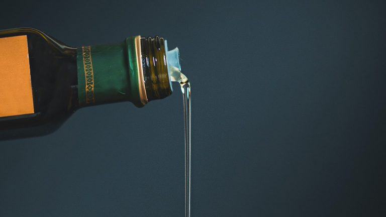 Closeup Photograph Of Olive Oil Being Poured From Dark Glass Bottle