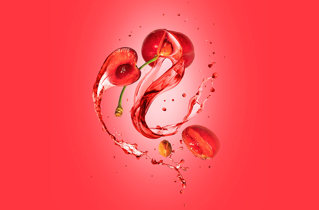 Photographic Illustration Of Fresh Cherries And Juice Splashing Against A Red Background