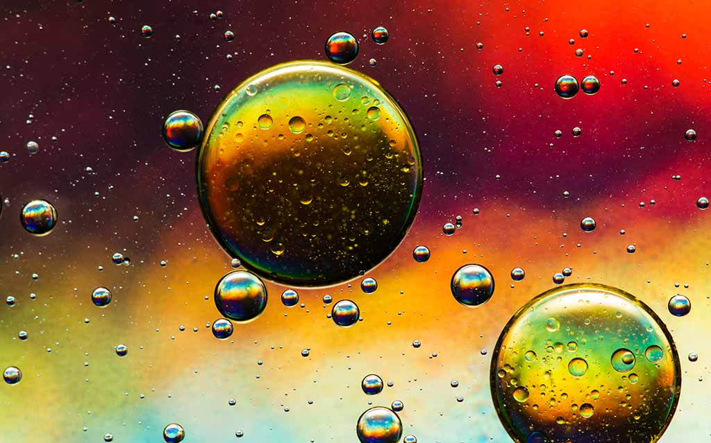 Abstract Colorful Closeup Of Liquid Oil Bubbles In Shades Of Red, Green, And Yellow