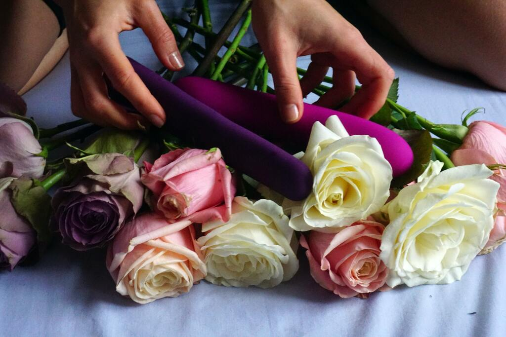 Close Up Photograph Of Woman's Hands Reaching For Phallic Sex Toys Laying On Bouquet Of Flowers