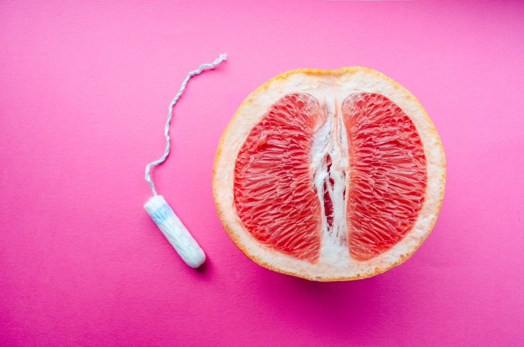 An Unused Tampon Laying Beside Half Of A Pink Grapefruit