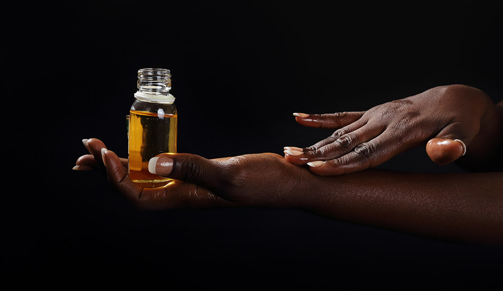 Closeup Photograph Of African American Hand Holding Vial Of Oil Being Rubbed Into The Skin