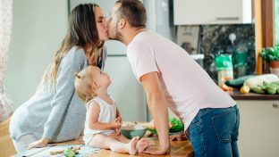 Photo Of A Couple Kissing In The Kitchen With A Baby On The Counter Between Them Looking Up At Them