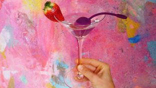 Photograph Of Hand Holding Martini Glass With Purple Cherry-Shaped Sex Toy, Body-Safe Concept
