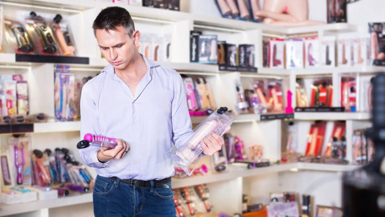 Photograph Of Confused Man Comparing Vibrators In A Sex Shop