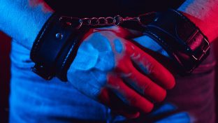 Moody Close Up Photograph Of Man's Hands In Leather Handcuffs