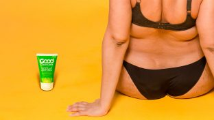 Rear View Photograph Of Woman Wearing Underwear With A Bottle Of Good Clean Love Almost Naked Lubricant Beside Her