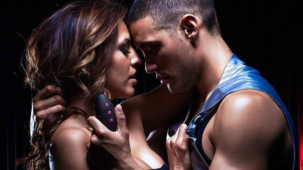 Photograph Of Seductive Couple Standing Face To Face, Man Holding Vibrator Remote