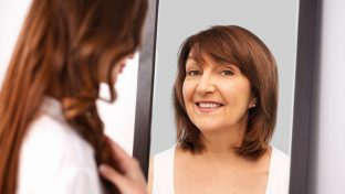 Image Of A Younger Woman Looking Into A Mirror And Seeing A Reflection Of Her Mother