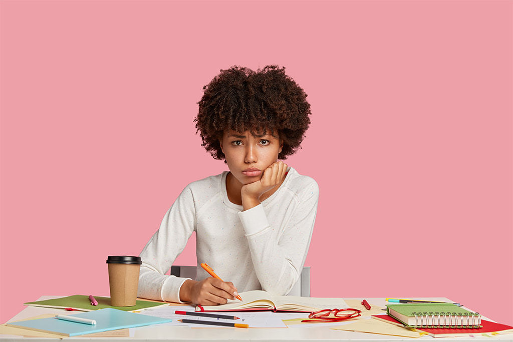 Concerned Young African American Woman Sitting At Desk With Coffee And Notebooks, Pencil In Hand