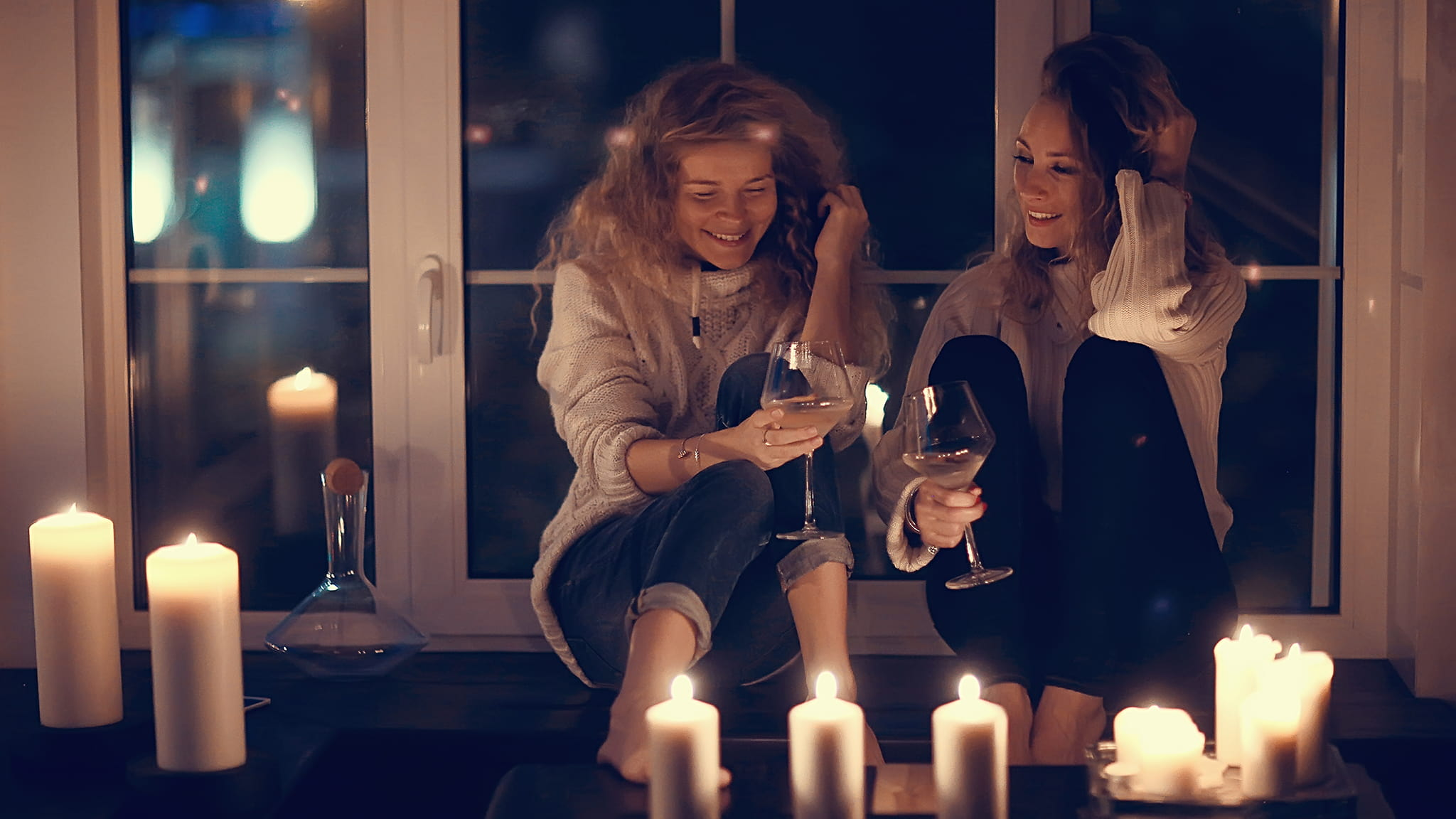 Two Women Smiling While Drinking Wine And Sitting Close Together In A Candlelit Room, Fun And Romance Concept