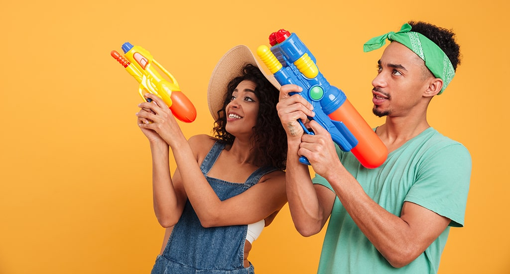 Photograph Of Woman And Main Aiming Squirt Guns In The Same Direction Against Orange Background