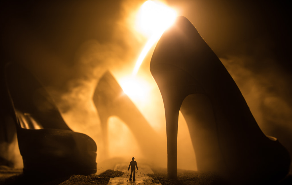 Surreal Concept, Silhouette Of Tiny Man Walking A Path Between Giant High Heel Shoes Against Smoky Golden Light