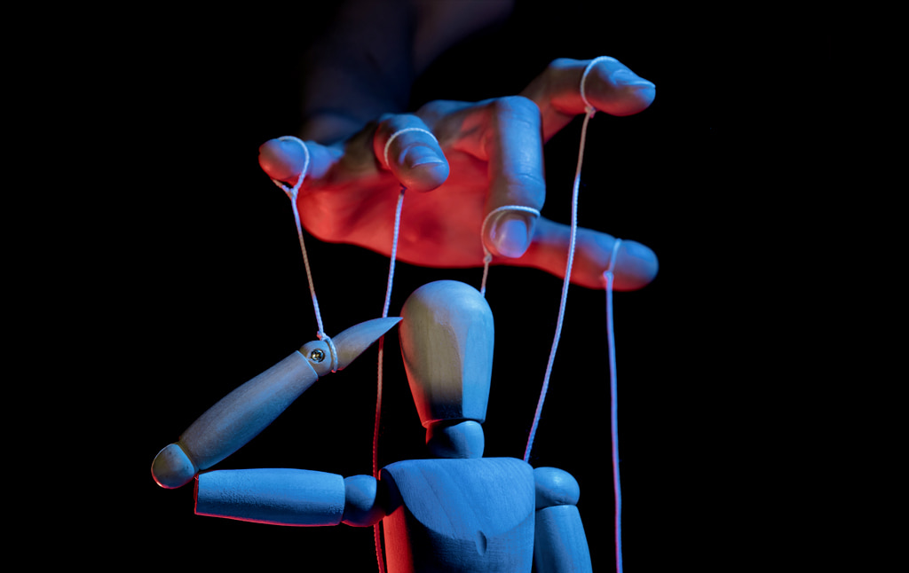 Moody Close Up Photograph Of Hand Controlling Wooden Marionette