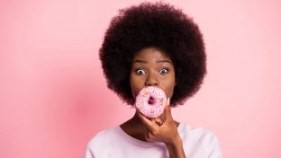 African American Woman Holding Pink Donut With Hole Placed Over Her Mouth, Analingus Concept