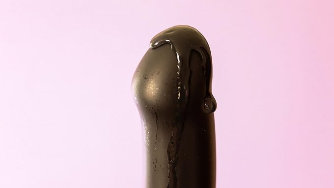 Closeup Photograph Of Smooth Black Dildo Tip Covered In Lube Against Pink Background