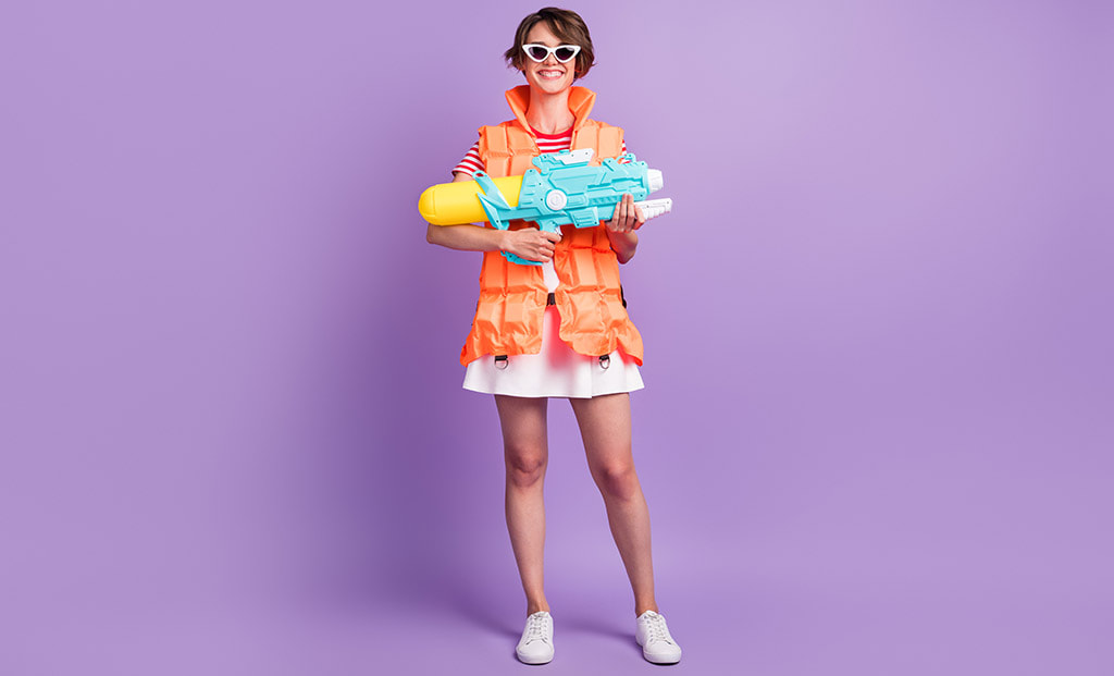 Photograph Of Beachy Woman Holding Giant Squirt Gun In Front Of A Purple Background