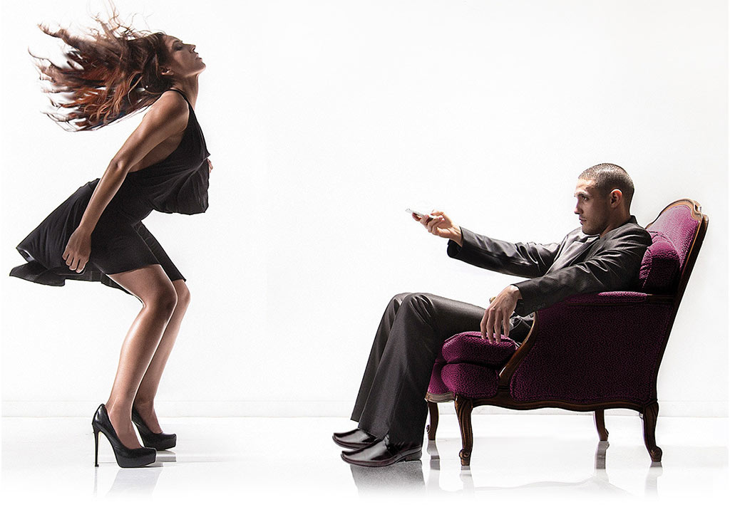 Photograph Of Woman Being Pleasured While Suited Man Sits In Front Of Her, Holding A Remote Control