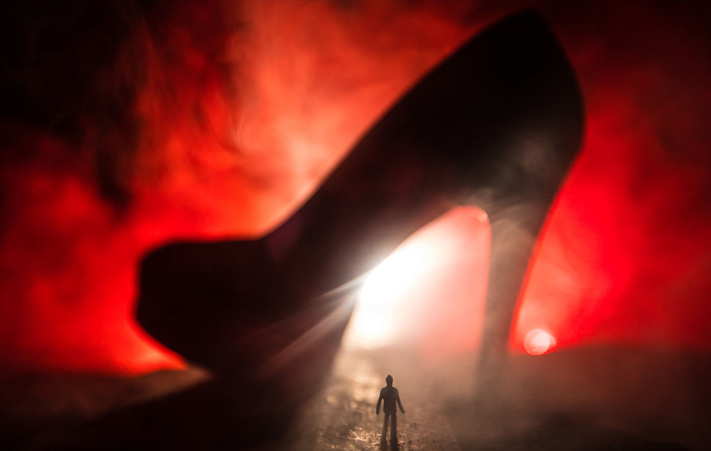 Surreal Concept, Silhouette Of Tiny Man Looking Up At A High Heel Shoe Against Deep Red Smoky Light
