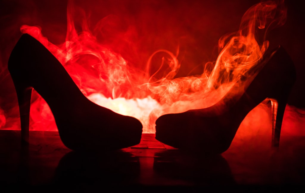 Silhouette Of Two High Heel Shoes Facing One Another Against Deep Red Flames, Heat And Passion Concept