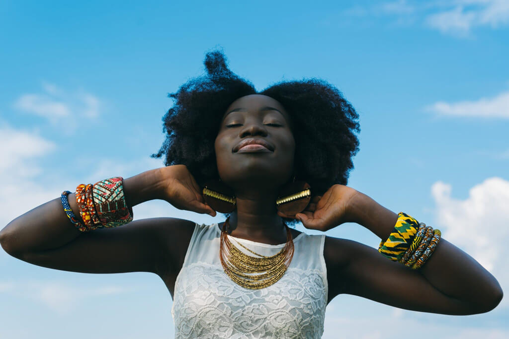 Young Black Woman With Closed Eyes Looking Up Confidently