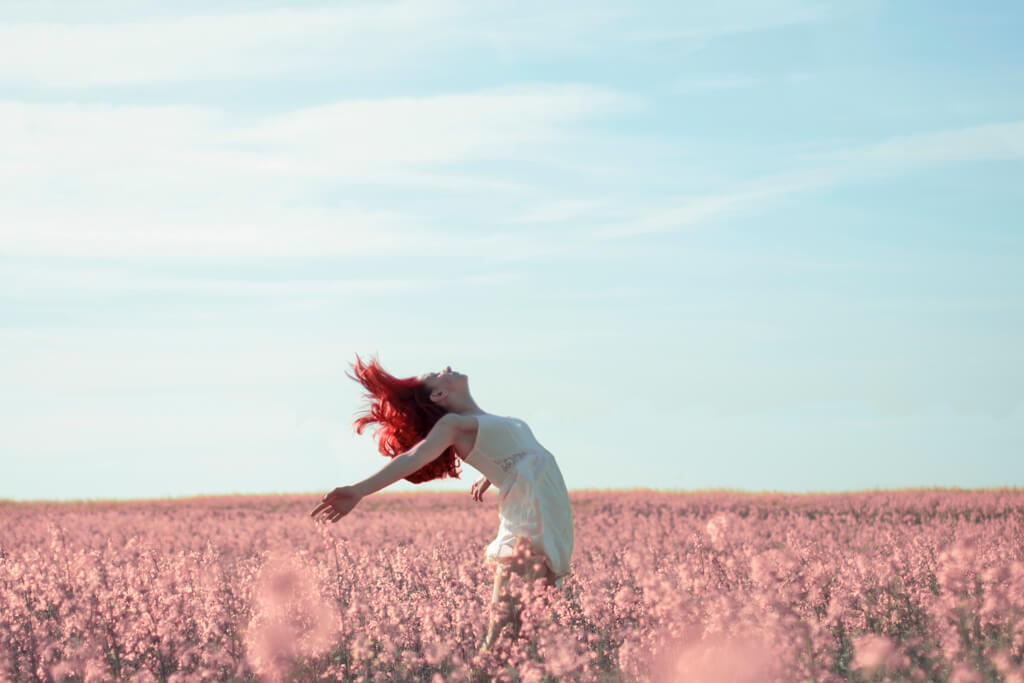 Young Woman In Field of Pink Flowers Arms Outstretched Empowered By Sexual Freedom
